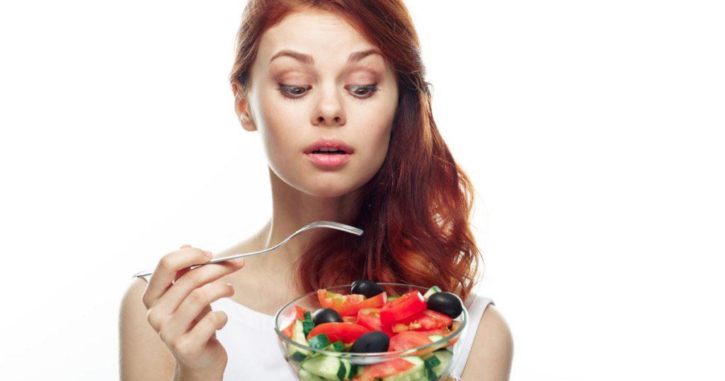 Eine junge Frau schaut auf ihren kleinen Salat in der linken Hand und ist kurz davor mit der Gabel in der rechten Hand in eine Tomate zu stechen. Sie schaut sehr skeptisch mit hochgezogenen Augenbrauen.