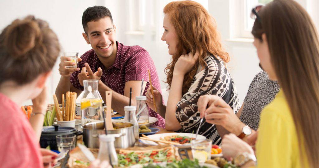 Freunde sitzen gemeinsam an einem großen Essenstisch und sitzen gemütlich beim Essen beieinander und sind fröhlich