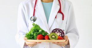 Eine Person im weißen Arztkittel und einem roten Stetoskop um den Hals hält in ihren Händen einen Holzteller mit pflanzlichen Lebensmitteln
