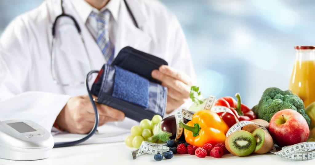 ein Arzt im Hintergrund des Bildes hat ein Blutdruckmessgerät in den Händen. Vor ihm auf dem Tisch sind viele bunte Gemüse- und Obstsorten zusammen gelegt