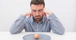 Ein Mann sitzt gelangweilt an einem Tisch und schaut auf einen grauen Teller, auf dem nur ein noch ungeschältes Ei liegt. Er stützt seinen Kopf mit seinen Händen und starrt auf das Ei.