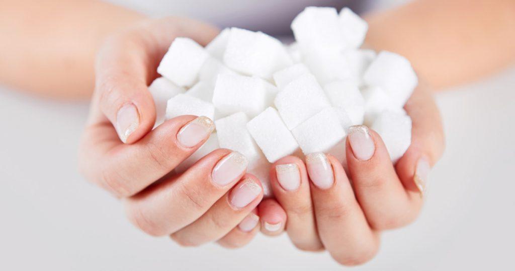 Zu sehen sind Frauenhände, die mit Würfelzucker gefüllt sind