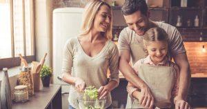 Ein junges Paar steht zusammen in der Küche und schneidet mit der Tochter Gemüse für einen Salat