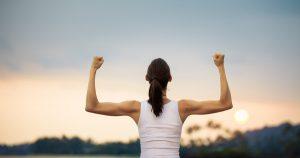 Eine durchtrainierte Frau steht vor einem Sonnenuntergang und spannt ihre Oberarme mit beidseitig gestreckten Armen an, um ihre Muskeln zu zeigen