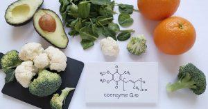 Lebensmittel, wie Orangen, Avocado, Brokkoli und Blumenkohl sind reich an Q10 und liegen nebeneinander. Darunter ist die chemische Molekülformel auf ein Blatt Papier gezeichnet.