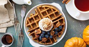 Eine Waffel mit Blaubeeren und einem Häubchen Sahne liegen auf einem Teller. Daneben liegen zwei Zierkürbisse, eine Tasse Tee und Ahornsirup in einem kleinen Kännchen