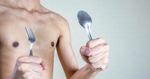 Der magere Oberkörper eines jungen Mannes ist zu sehen. Er hält Gabel und Löffel in jeweils einer Hand hoch und signalisiert damit, dass er essen und zunehmen möchte.