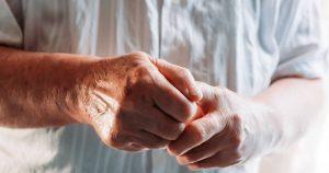 Eine ältere Frau hält ihre von Rheuma betroffenen Hände vor ihren Oberkörper.