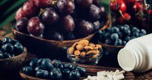 Abgebildet sind dunkle Trauben, Blaubeeren und Kirschen, die den sekundären Pflanzenstoff Resveratrol enthalten. Mandeln mit Polyphenolen sind auch abgebildet. Daneben liegen weiße Kapseln, die Resveratrol künstlich enthalten.
