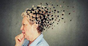 Eine ältere Frau ist im Profil abgebildet. Sie hält sich mit zwei Fingern die Stirn, hat die Augen geschlossen und ihr Hinterkopf ist in davonfliegenden Puzzleteilen abgebildet.