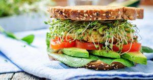 Ein Sandwich mit Sprossen, Avocado, viel Gemüse, einem Haferbratling und Vollkornbrotscheiben ist dargestellt.