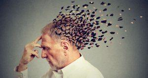Ein älterer Mann ist im Profil abgebildet. Er hält sich mit zwei Fingern die Stirn, hat die Augen geschlossen und sein Hinterkopf ist in davonfliegenden Puzzleteilen abgebildet.