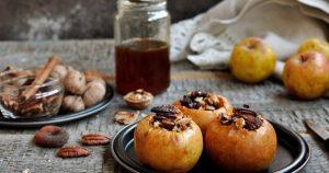 Drei gefüllte Bratäpfel mit Nüssen und Honig liegen im Vordergrund auf einem Teller. Im Hintergrund ist ein Glas Punsch zu sehen und daneben ein Teller mit Walnüssen.