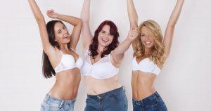 drei selbstbewusste Frauen in Jeans und weißen BHs recken ihre Arme hoch und sind glücklich