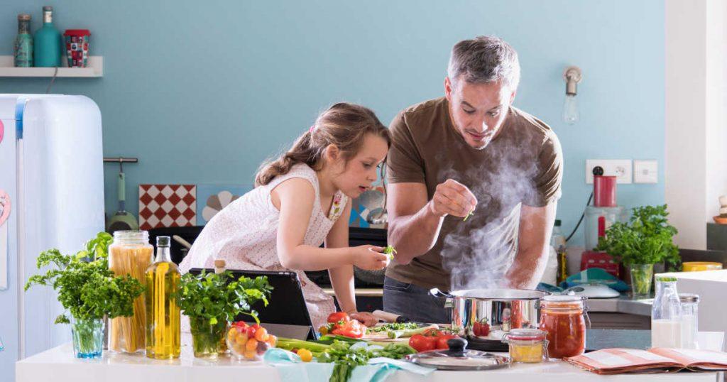 Ein Vater steht mit seiner Tochter zusammen am Herd und sie kochen gemeinsam. Um sie herum stehen viele frische Lebensmittel verteilt