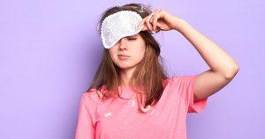 Eine junge Frau hebt ihre Schlafmaske mit der linken Hand hoch und schaut sehr müde. Auf ihrem rosafarbenen Schlafshirt liegen ein paar Federn.