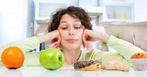 Eine junge Frau hat ihre Ellenbogen auf einen Tisch abgestützt und schaut vor sich wo eine Orange, ein Apfel und daneben ein Donut, Croissant und Muffin liegen