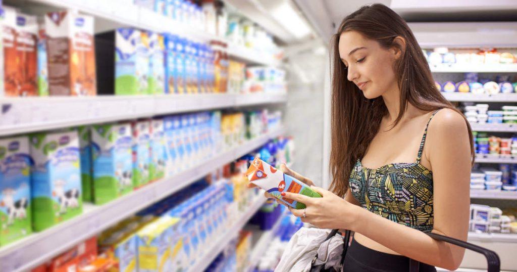 Eine junge Frau steht vor einem Kühlregal und checkt die Etiketten nach Nährstoffangaben