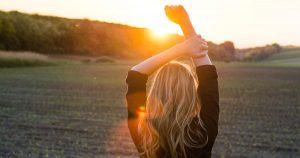 Eine junge Frau reckt die Arme empor und steht einem Sonnenaufgang gegenüber auf einer Wiese