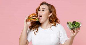 Eine junge übergewichtige Frau hält in der rechten Hand einen Burger, in den sie reinbeißen will. In der linken Hand, hält sie einen Salat weiter von sich fern.