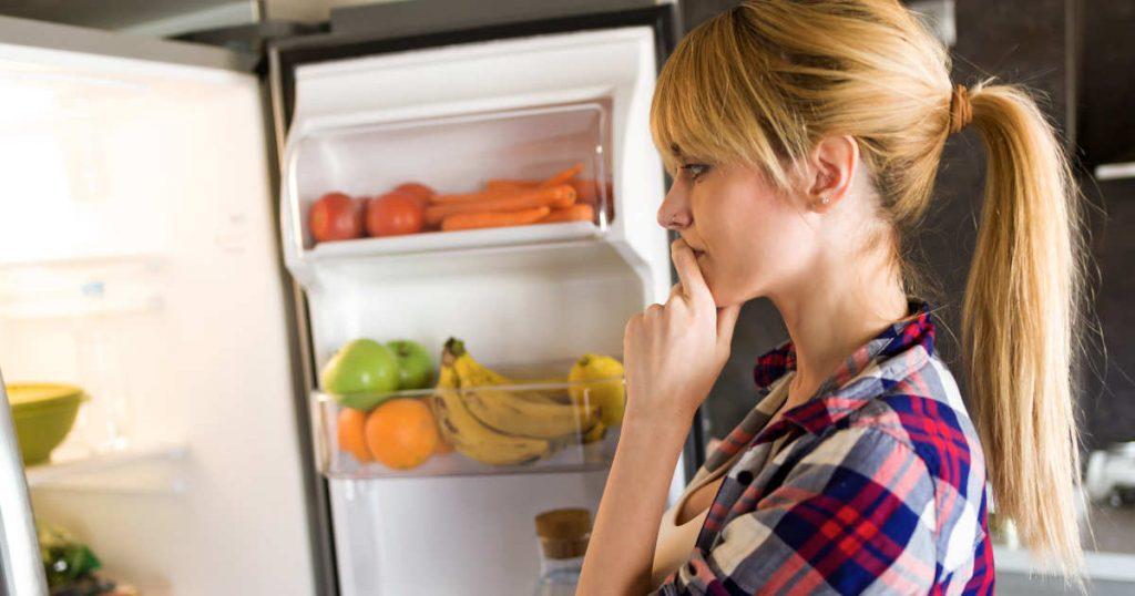 Eine Frau mit Pferdeschwanz steht vor dem offenen Kühlschrank, der mit buntem Obst und Gemüse gefüllt ist. Sie überlegt, was sie essen soll.