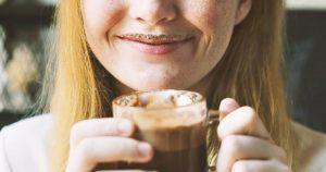 Eine junge Frau hält einen Glasbecher mit Kakao in ihrer Hand. Sie grinst und hat über ihrer Lippe einen Kakaobart