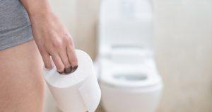 Eine Frau in kurzer Hose hält in der rechten Hand eine Rolle Klopapier und steht in Bad gegenüber einer Toilette