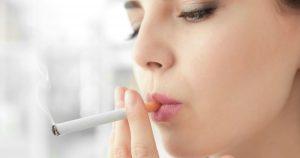 Eine junge Frau ist im Profil zu sehen, wie sie sich gerade eine Zigarette anzündet